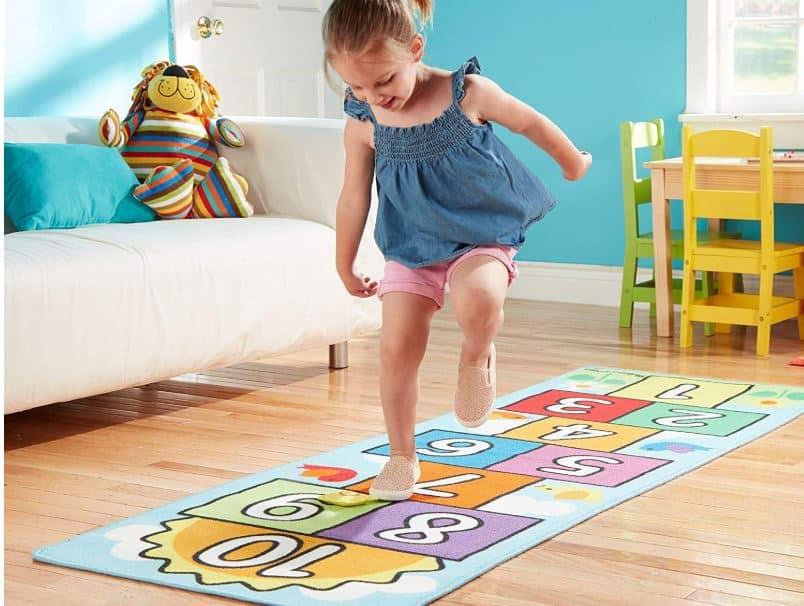 petite fille jouant sur un tapis marelle
